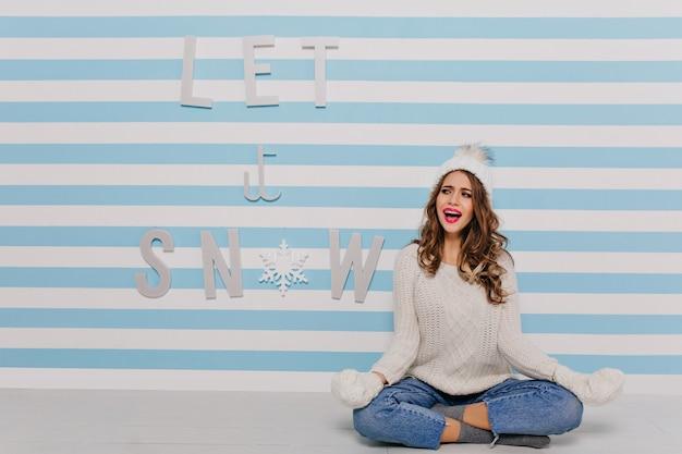 瞑想のためのポーズで床に座っている感情的な女の子。碑文「雪を降らせて」の上の暖かいスタイリッシュな服装の女性