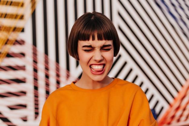주황색 스웨터에 갈색 머리를 한 감정적인 소녀는 밖에서 재미있는 얼굴을 만든다