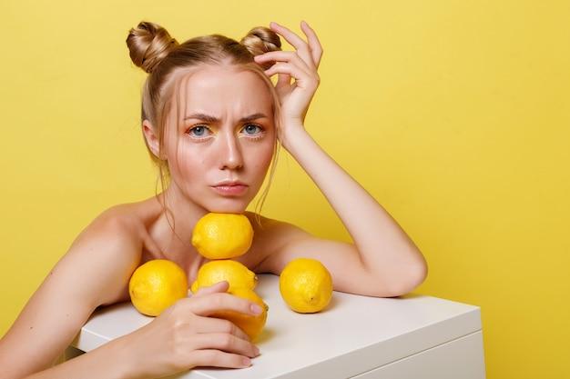 노란색 벽에 레몬과 감정적 인 여자 프리미엄 사진