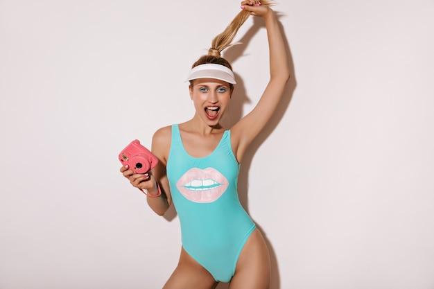 트렌디 한 파란색 수영복과 분홍색 카메라로 포즈를 취하고 격리 된 벽에 카메라를 찾고 흰색 모자에 긴 금발 머리를 가진 감정적 인 소녀