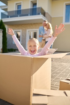 Emotional girl with raised hands sitting in box