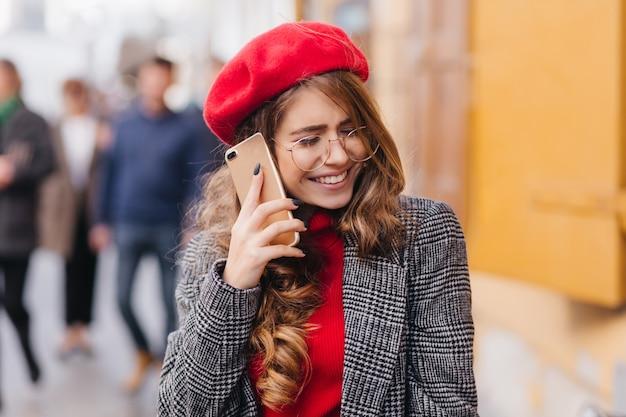 通りを渡って歩いて、電話で話している光沢のある髪の感情的な女の子