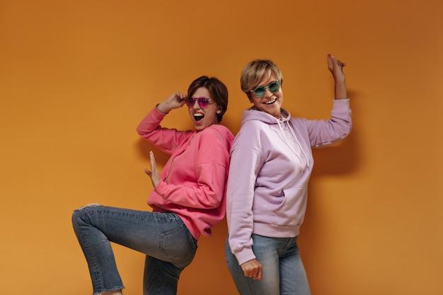 Эмоциональная девушка в солнцезащитных очках в розовой толстовке смеется и позирует со старушкой в сиреневой толстовке с капюшоном на оранжевом фоне.