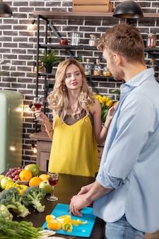 감정적 인 여자 친구. 와인을 마시고 저녁 식사를 위해 샐러드를 요리하는 그녀의 남자와 이야기하는 감정적 인 금발의 여자 친구