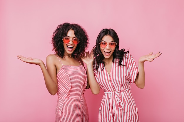 Emotional girls make surprised face expression. lady in summer pink sunglasses posing for portrait.