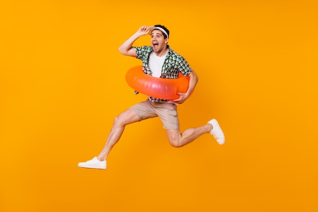 Emotional guy in high spirits jumps on orange space with inflatable circle and takes off his cap.
