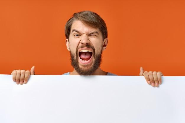 그의 손에 종이의 흰 시트를 들고 감정적 인 남자 포스터 mockup 광고 기호입니다. 고품질 사진