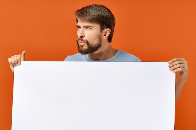 Эмоциональный парень держит в руках белый лист бумаги