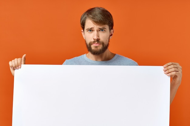 Emotional guy holding a white sheet of paper in his hands poster mockup advertising sign.