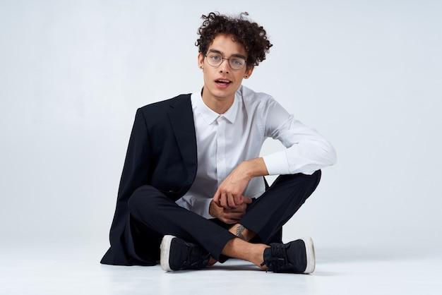 Эмоциональный парень в классическом костюме сидит на полу в светлой комнате в очках на лице портрета