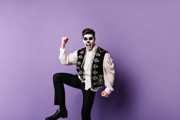 メキシコの服を着た感情的な男は勝利を喜ぶ。ライラックの壁にポーズをとる頭蓋骨マスクを持つ男の写真。