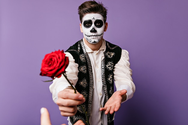 Эмоциональный парень тянется к любимой. портрет мужчины с раскрашенным лицом в мексиканской жилетке с розой в руках.