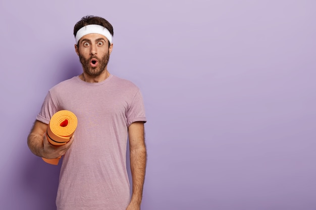 Emotional guy with bristle wears headband and purple t shirt, gets ready for aerobics