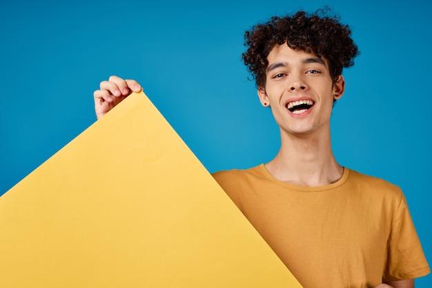 Эмоциональный парень с кудрявыми волосами держит в руках желтый плакат, рекламирующий синий фон