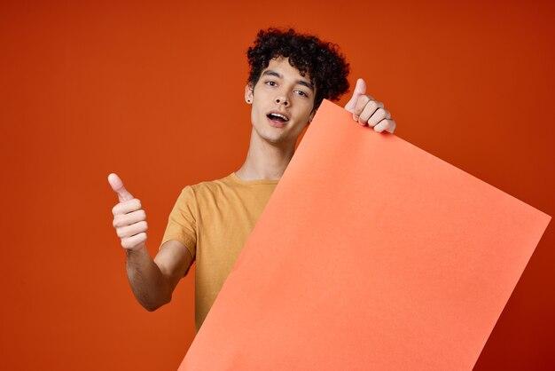 Эмоциональный парень с вьющимися волосами с оранжевой пустой бумагой на руках