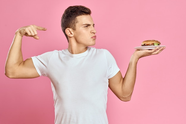 Emotional guy with hamburger on a plate and white t-shirt pink background cropped view of fast food calories. high quality photo