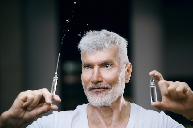 手に注射器でワクチン接種された感情的なハンサムな白髪の年配の男性。免疫化とヘルスケアの概念