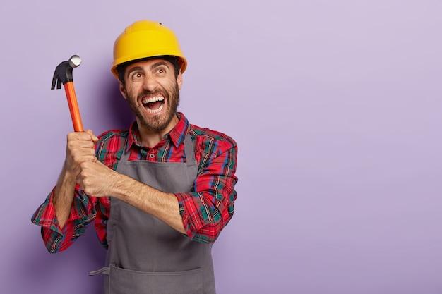 감정적 인 핸디는 양손으로 망치를 들고 노동 작업을 준비하고 노란색 보호 헬멧, 캐주얼 작업복을 착용하고 감정적으로 소리를 지 릅니다.