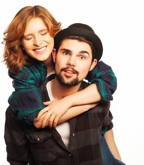 感情的、幸福、人々の概念:幸せな愛情のあるカップル。若い男が彼のガールフレンドを便乗します。ホワイトスペースの上。特別なファッショナブルな調色写真。