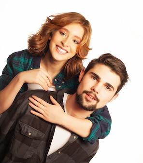 感情的、幸福と人々の概念:幸せな愛情のあるカップル。彼のガールフレンドを便乗している若い男。白い背景の上にスタジオで撮影しました。特別なファッショナブルな調色写真。