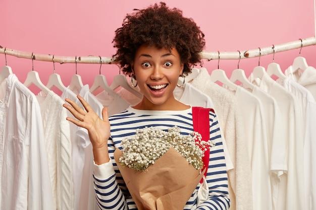 부케와 정서적 행복 곱슬 머리 여자, 흰색 우아한 셔츠를 선택, 레일 위에 선다.