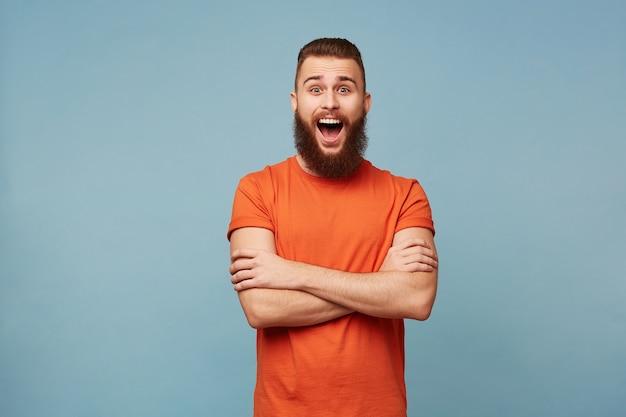 무거운 수염을 가진 정서적 행복 흥분 재미 있은 남자 팔을 넘어 서서 파란색에 고립 된 빨간 티셔츠를 입은 놀라움에 입을 열어 와우 표현을 보여줍니다.