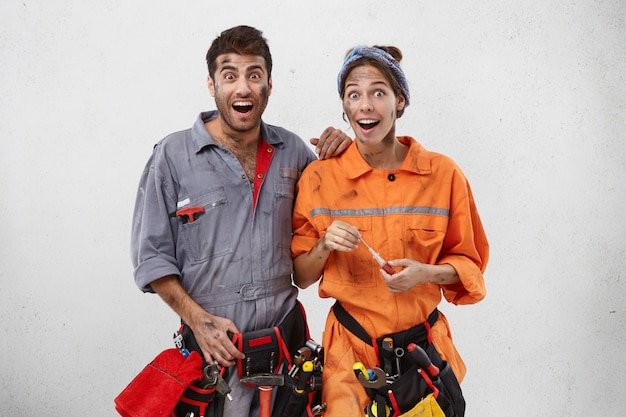 Emotional happy female and male carpenters look with excitement or surprisment