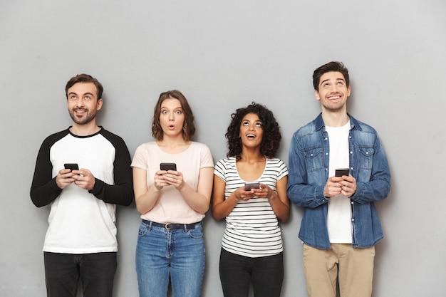 よそ見携帯電話を使用して友人の感情的な幸せなグループ。