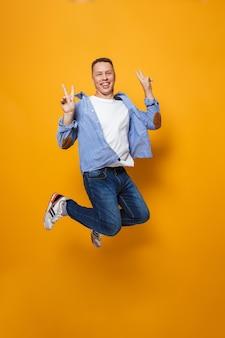 Эмоциональный счастливый человек, прыгающий, делает жест мира.
