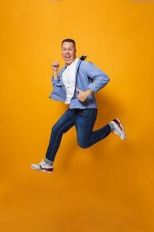 Эмоциональный счастливый человек прыгает, делает палец вверх жест.