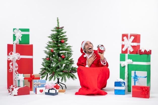 地面に座って、白い背景の上の贈り物や装飾されたxsmasツリーの近くに時計を表示して上を見て感情的な幸せなサンタクロース