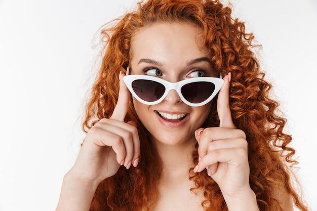 サングラスをかけている感情的な幸せな若い赤毛の巻き毛の女性。