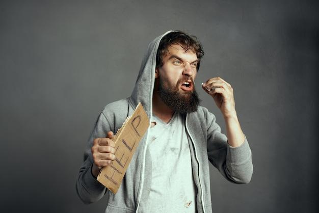 あごひげのサインを持つ感情的なホームレスの男性はお金の問題を助けます
