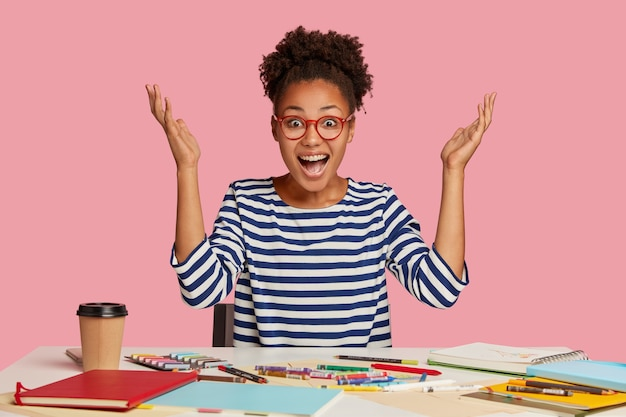 Emotional illustrator raises hands in eureka, exclaims with happiness, has nice idea for masterpiece, works at table with notepad, crayons, coffee, wears striped sweater, isolated over pink wall