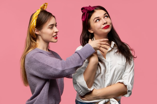 Emotional infuriated young woman grimacing and screaming expressing negative reaction being angry holding hand on neck of her girlfriend with malevolent gloating smile as if trying to strangle her