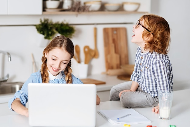 감정적 인 아이. 그녀의 노트북을 사용하여 공부하는 동안 그의 여동생이 말하는 것에 대해 꽤 기뻐 보이는 호기심 많은 유머러스 한 밝은 소년