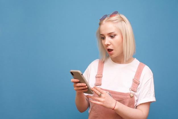 Эмоциональная дама в яркой одежде с телефоном в руке изолирована на синем