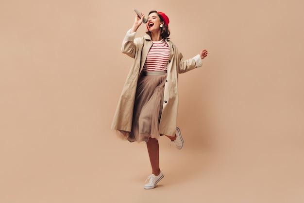 파리 스타일의 옷을 입은 감정적 인 아가씨가 베이지 색 배경에 노래합니다. 스트라이프 스웨터와 흰색 운동화 포즈에 밝은 입술을 가진 매력적인 여자.