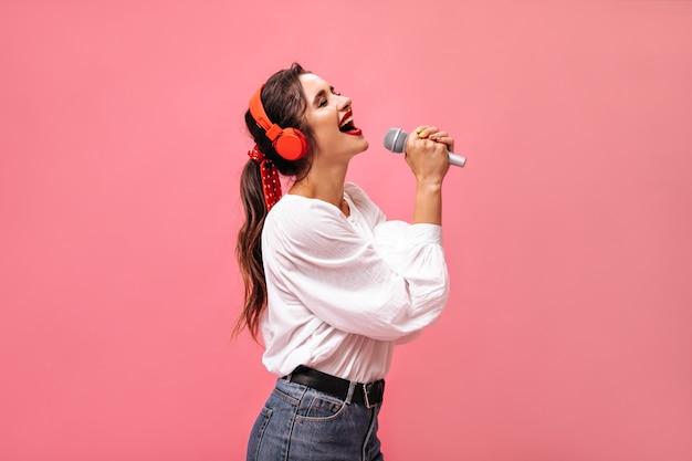 マイクで歌っている赤いヘッドフォンの感情的な女性。白いブラウスと黒帯のポーズのジーンズで明るい美しい女の子。