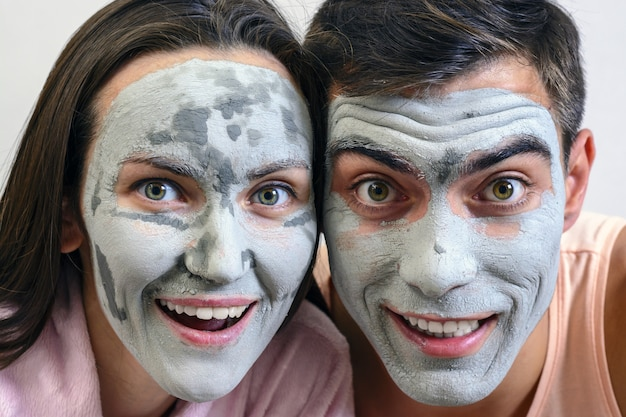 Emotional large portrait of a married couple in masks for the face of clay. day spa, wellness, skincare