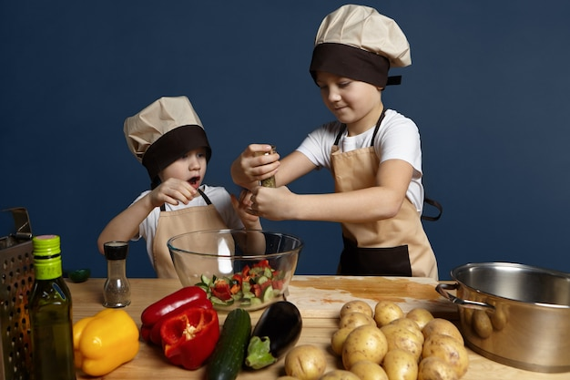 Ragazzino emotivo in piedi al tavolo della cucina con patate, peperoni, cetrioli e melanzane, aprendo la bocca eccitato, guardando il suo fratello anziano che mette troppe spezie nella ciotola di insalata