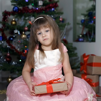 Emotional little cute girl in a pink dress is sad by the christmas tree. the child does not like the gift