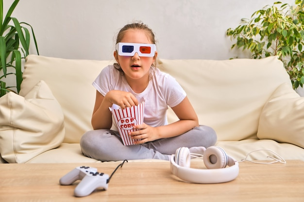 Emotional little girl in 3d movie glasses eating popcorn from striped bucket and watching tv at home