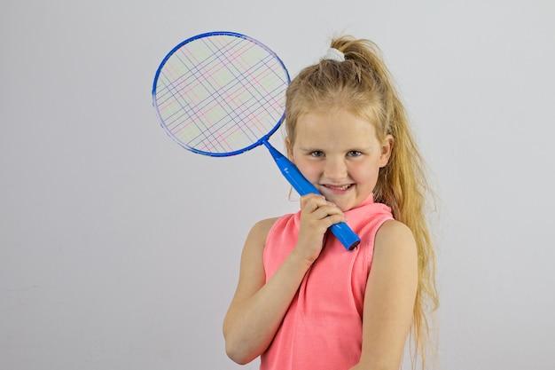 Эмоциональная маленькая девочка держит теннисную ракетку. концепция профессионального спорта для детей