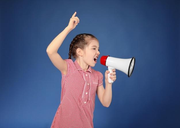 Emotional little girl shouting into megaphone on color