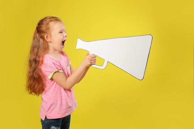 Emotional little girl shouting into paper megaphone on color