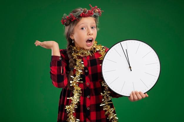 Эмоциональная маленькая девочка в рождественском венке в клетчатом платье с мишурой на шее, держащая настенные часы, смотрящая в камеру, изумленная и удивленная с поднятой рукой, стоя на зеленом фоне