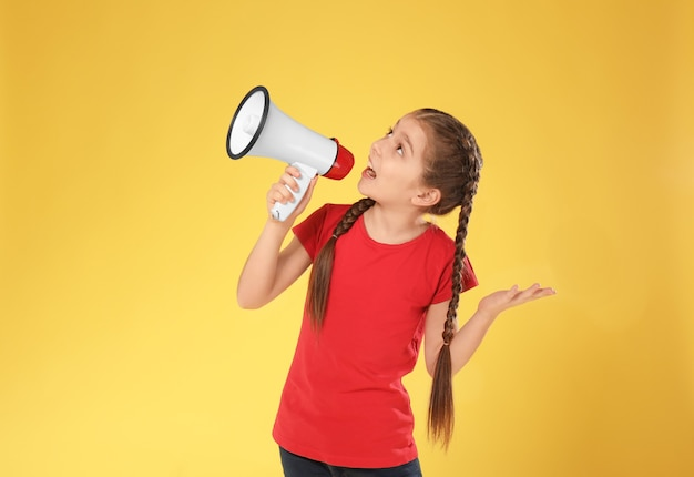 Emotional little girl with megaphone on color