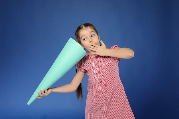 Emotional little girl with paper megaphone on color