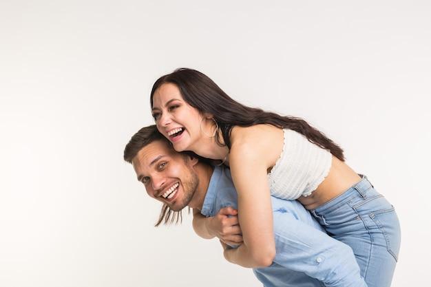 정서적, 사랑 이야기 및 사람들 개념-젊은 여성이 그 남자를 등에 올라 행복하고 미소 짓습니다.